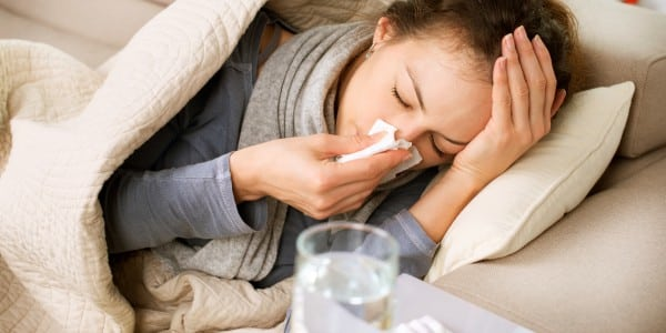 Woman on Couch with the flu Blowing Her Nose